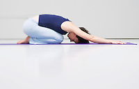 A woman on a yoga mat in childs pose.