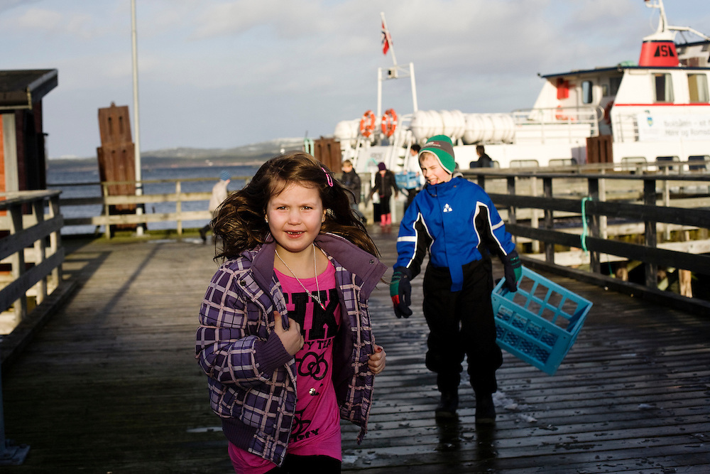 Girl running from the boat at Kjorsvikbugen. A boy has returned a case of books...Photo by Knut Egil Wang /MOMENT