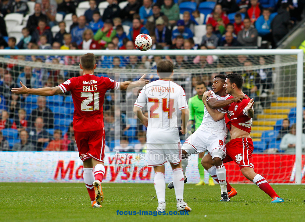 Sean Morrison of Cardiff City and Britt Assombalonga of Nottingham Forest during the Sky Bet Championship match at the Cardiff City Stadium, Cardiff<br /> Picture by Mike  Griffiths/Focus Images Ltd +44 7766 223933<br /> 18/10/2014