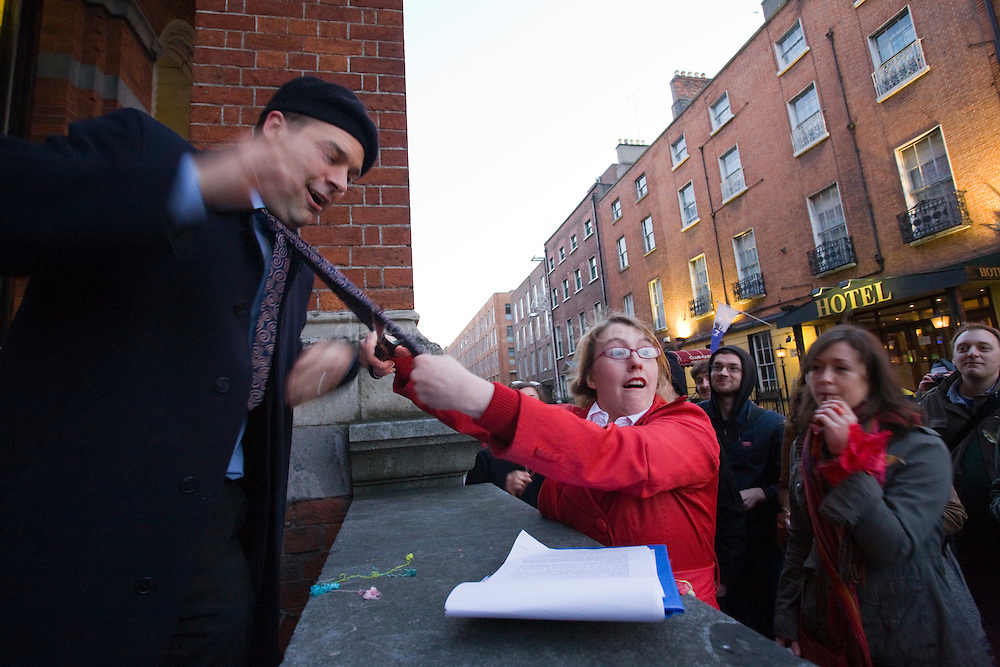 Frenchman has his tie cut by woman, Alliance Francaise, Dublin, during Walking Tour of Places of No Historical Interest Festival of Fools, April 1st 2009, marking April Fool's Day, and the 43rd anniversary of the death of Irish author Flann O'Brien.