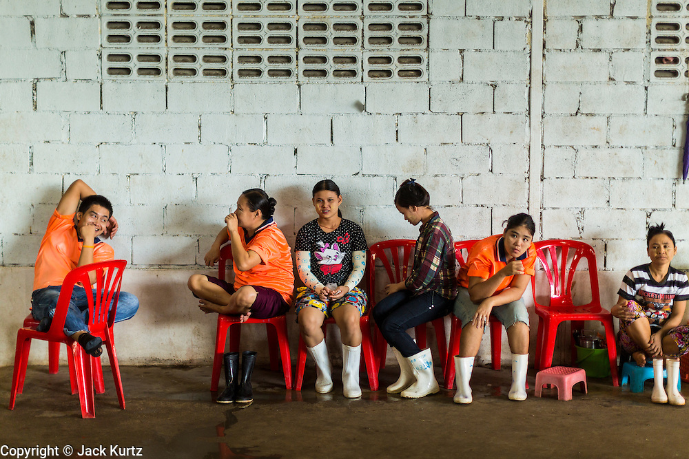 20 JUNE 2014 - SAMUT SAKHON, SAMUT SAKHON, THAILAND: Burmese migrant workers relax in a shrimp processing center in Samut Sakhon. Hundreds of thousands of migrant workers from Myanmar work in the Thai fishing industry. Samut Sakhon, (sometimes still called Mahachai, its historical name) is a large fishing port. Many Burmese live in the town and work in the fish process plants. Although hundreds of thousands of Cambodians fled Thailand last week after the military coup, the Burmese workers have stayed and are still working in many Thai towns.    PHOTO BY JACK KURTZ