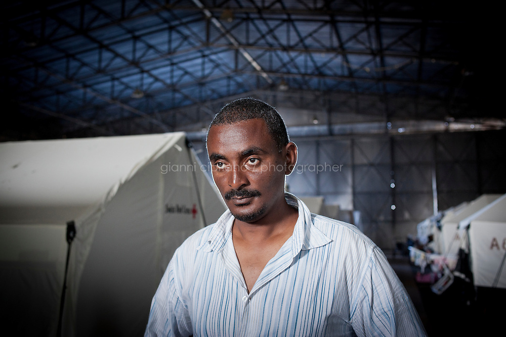 HAL FAR, MALTA - JUNE 21: Dawit (right), a 35 years immigrant old from Ethiopia, and Michael (center), a 25 years old immigrant from Eritrea, are here by the Swiss Red Cross tents inside the Hangar Open Center in Hal Far (which translates as &quot;Rat's Town&quot;) on June 21, 2011. <br /> <br /> Dawit was a language teacher in Tripoli and lived well, with no problems until the crisis started. He arrived in Malta on March 29th on a boat with 80 people after crossing the sea for 34 hours. &quot;Once the UN resolution against Libya was signed there were State TV announcements (also in English) that announced that migrants were free to leave the country. It wasn't possible before that date because of the agreement between Italy and Libya&quot;. No police or army forced them to leave, but there was some kind of general pressure to get sub-saharan migrants out of the country and to have them leave by boat. In Dawit's case, his landlord told him he had one day to leave his apartment. &quot;Buses in Tripoli were collecting people and deporting them&quot;, Dawit says. They couldn&rsquo;t go towards Tunisia or Egypt, only towards to the coast. Other sub-Saharans were able to flee to Tunisia, but there aren't any Ethiopian embassies in Libya, so Ethiopians in Libya don't have any documents that allowed them to stay in the country or officially cross borders. Once they arrived at the port they didn't pay any fixed fee but all they had was confiscated, including food and water. A boat was given to them and they left. &quot;People had bought food and water for their journey, but everything was confisfacted. I was lucky, because it took me only 34 hours to arrive in Malta, but it took these guys (indicating Michael, 25, and Mubarak, 23, both from Ethiopia, standing next to him - not in this picture) 10 days to arrive&quot;, Dawit says.Dawit continues: &quot;Life was good in Libya. We were all supporting our families. If wanted we could have left before, when everybody was leaving