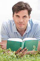 Portrait of young man holding book while lying on grass