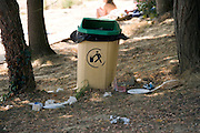 public garbage container with various waste spilled around on the ground