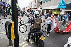London, UK. 17 July, 2019. A motorcyclist behaves aggressively towards climate activists from Extinction Rebellion briefly blocking a road to enable a Critical Mass bicycle ride from Waterloo Millennium Green to Hammersmith Town Hall to pass. Activists on the ride on the third day of their 'Summer uprising' have three demands for Hammersmith and Fulham Council: to pass the proposed motion to declare a Climate Emergency; to keep Hammersmith bridge closed to vehicles; and to commit to safer cycling routes.