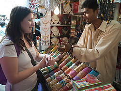Tourist buying bangles at stall in Mysore market.