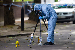 A forensics investigator collects evidence at the scene outside a block of flats at 65 Finborough Road, adjoining Cathcart Road, Chelsea following the fatal stabbing on the night of May 30th 2018 of a man in his forties, said to be a delivery driver who refused to hand over his cash to robbers. London, May 31 2018.