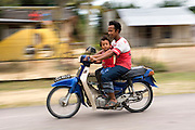 A father and his daughter ride a motor scooter in Johore, Malaysia. A motor scooter is one of the most economical and popular forms of transport in Malaysia, where safety regulations are rarely enforced.
