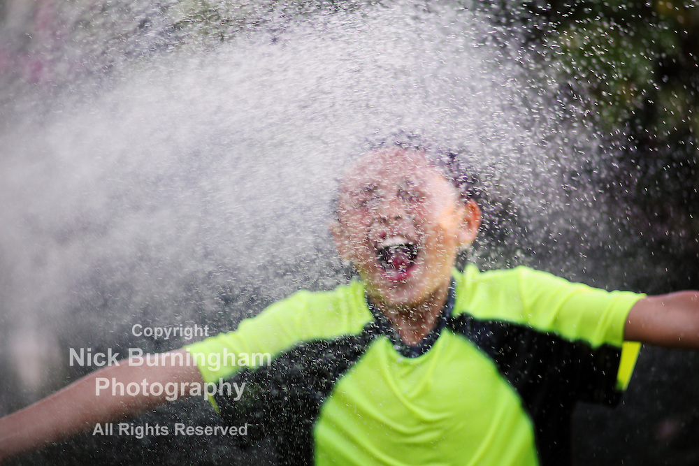 Young boy playing with sprayed water from hose - EXCLUSIVELY AVAILABLE HERE