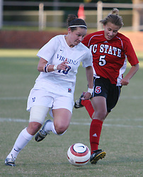 UVA midfielder Sarah Huffman (#10) dribbles the ball up field against NC State's Tami Krzeszewski.  Huffman had two shots, one on goal in UVA's 2-0 ACC victory over North Carolina State.
