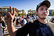 30 NOVEMBER 2011 - PHOENIX, AZ:    An anti-ALEC protester covered in pepper spray residue stands in front of a line of Phoenix police after they pepper sprayed a crowd at a protest in Phoenix Wednesday. Police pepper sprayed the crowd several times and arrested six or seven people during the melee.  About 300 people picketed the American Legislative Exchange Council (ALEC) conference at the Westin Kierland Resort and Spa in Phoenix, AZ, Wednesday. The protesters claim ALEC, a conservative think tank, violates its tax exempt status by engaging in lobbying, a charge ALEC officials deny. Many conservative pieces of legislation, like Arizona's anti-immigration bill SB1070, originate with ALEC conferences (SB 1070 originated at an ALEC conference several years ago). Many of the protesters are also members of the Occupy movement.   PHOTO BY JACK KURTZ