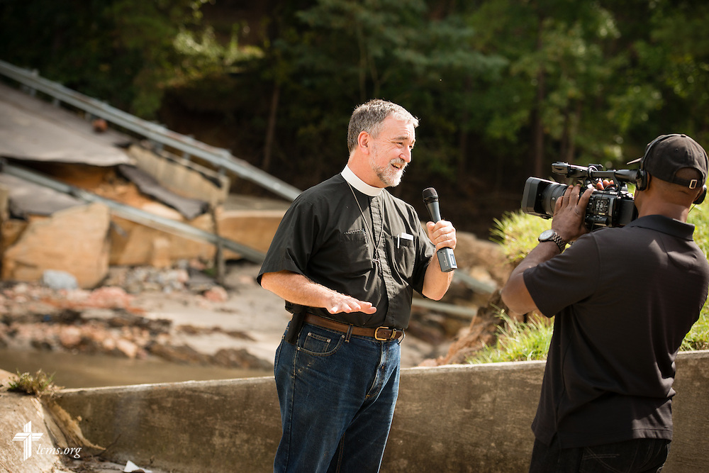 The Rev. Christopher Burger, pastor of Holy Trinity Lutheran Church in Columbia, S.C, gives a television interview to a local CBS affiliate next to flood damage on Friday, Oct. 9, 2015, in Columbia, S.C. LCMS Communications/Erik M. Lunsford