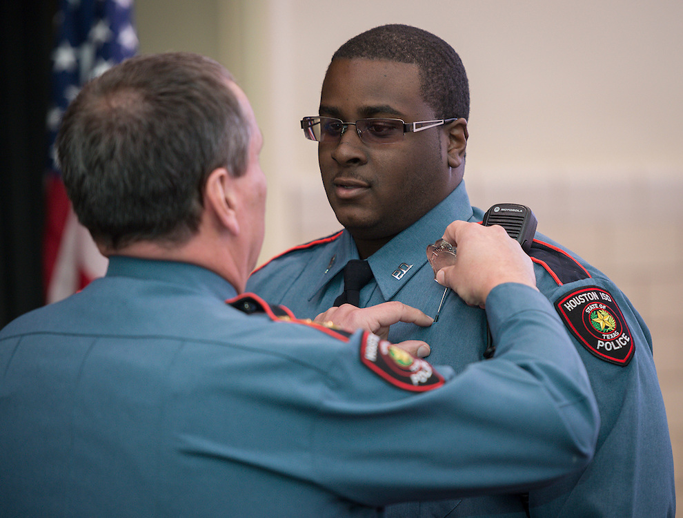 Damion Williams, right, receives his badge from Chief Mock during a swearing-in ceremony for new officers at the Houston ISD Police Department, March 3, 2014.