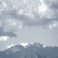 The snowcapped peak of Mount San Jacinto in the San Jacinto Mountains with clouds over the mountains.