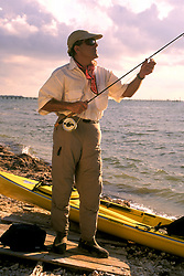 Stock photo of a man on shore standing beside his kayak and irunning his leader through the guides.