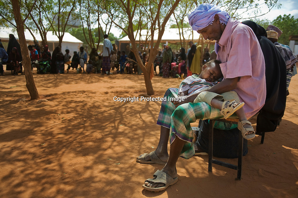 A man holds his child as they wait during the reception process at the Ifo refugee camp in Dadaab, Kenya, August 19, 2011. The Ifo settlement is the oldest of the camps in Dadaab, dating back to the early 1990's, but it has swelled in recent months due to Somalis fleeing the drought and famine in their war-torn country.