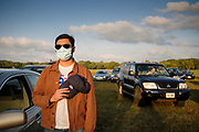 12 SEPTEMBER 2020 - DES MOINES, IOWA: RUNAL A. PATEL stands next to his car with his hand over his heart during the Pledge of Allegiance at the Polk County Democrats Steak Fry in Waterworks Park in Des Moines. The Steak Fry is the largest fundraiser of the year for Polk County Democrats. This year nearly 1,000 people attended. The Steak Fry observed public health guidelines. Normally the Steak Fry is a picnic but this year people stayed in their cars while meals were brought to them and they wore masks when they were outside of the cars. Most of the speakers appeared via online speeches.    PHOTO BY JACK KURTZ