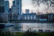 "Germany banned gatherings of more than 2 people called ""social distancing"" because of the coronavirus. A couple sitting at the shore of river Main in Frankfurt which is very empty on a - normally very busy - Thursday evening."