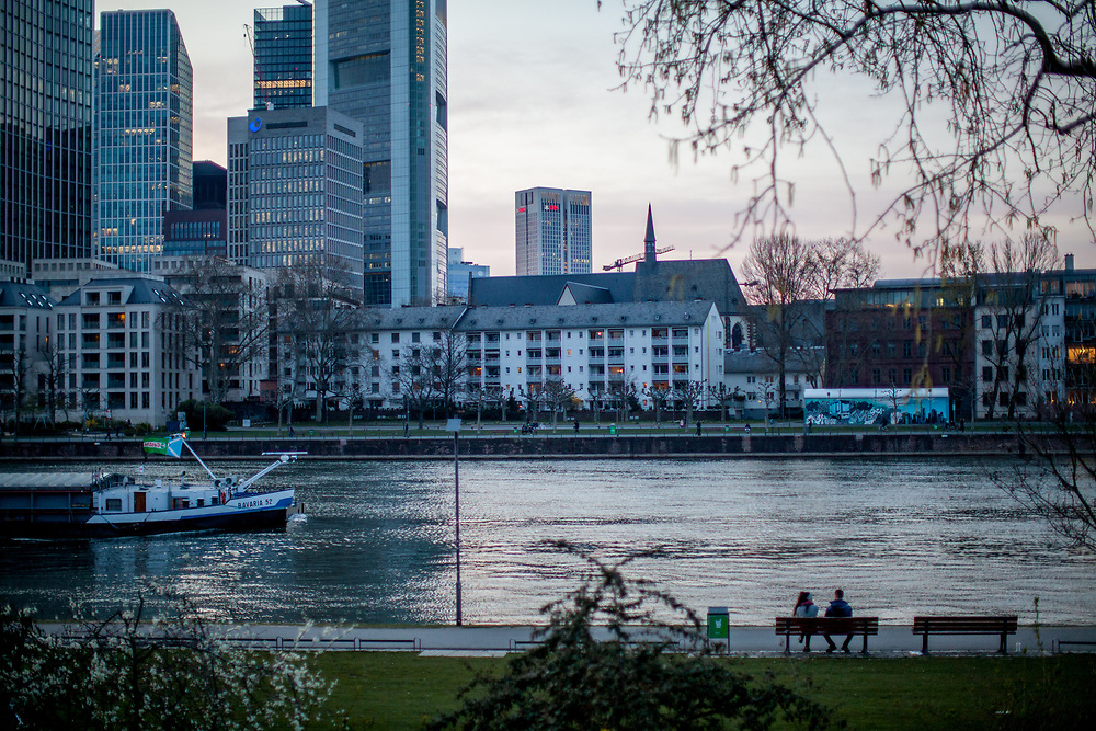 """Germany banned gatherings of more than 2 people called """"social distancing"""" because of the coronavirus. A couple sitting at the shore of river Main in Frankfurt which is very empty on a - normally very busy - Thursday evening."""