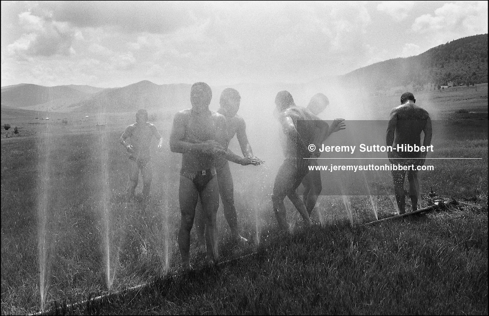 "Wrestlers cool off in a sprinkler system after their morning training session at Suj training camp, prior to competing in the annual countrywide Naddam Festival. The Naddam Festival is the festival of the ""three manly sports""-horse riding, archery and wrestling. The winner of the main Naddam wrestling tournament, held in the capital Ulaan Baatar, goes on to achieve national fame, and receives lucrative endorsement contracts."