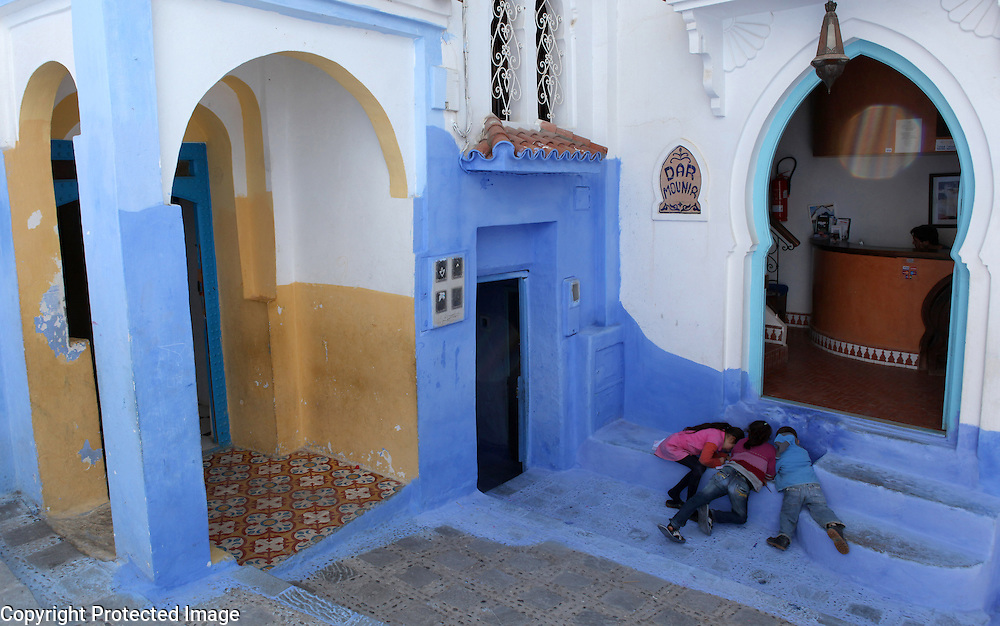 """Children do their homework on the steps of the hotel their family runs in Chefchaouen, Morocco, whose """"medina"""" (old city) is famous for its striking blue walls."""