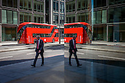 City street corner plate glass reflection of red double-decker Routemaster London bus.