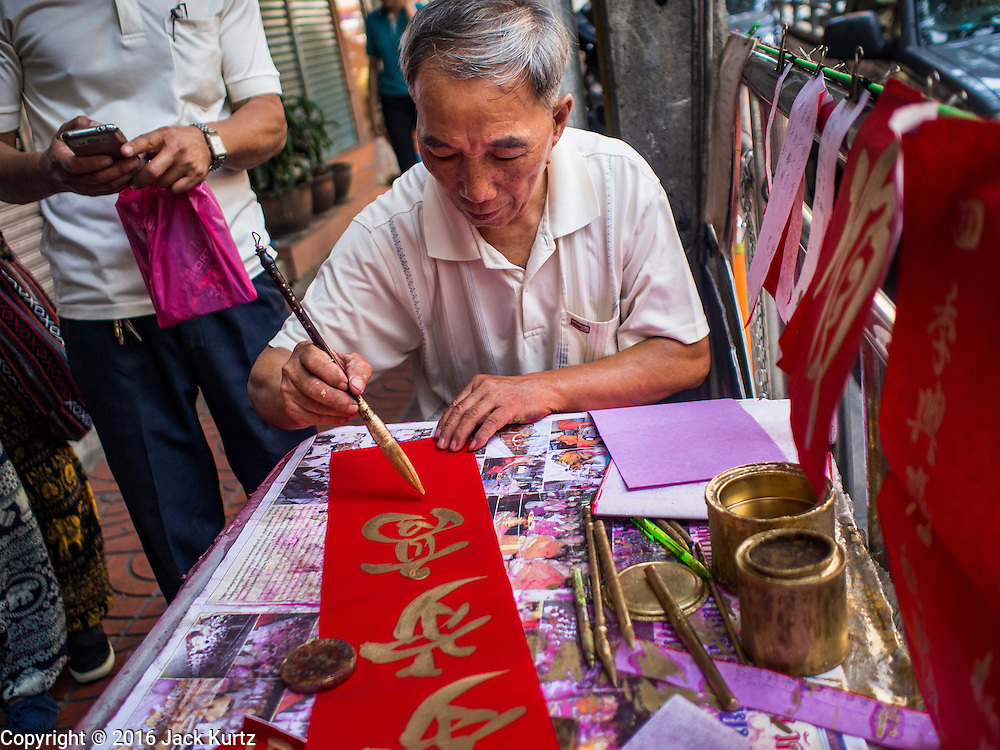 """04 FEBRUARY 2016 - BANGKOK, THAILAND:  A Chinese calligrapher writes out New Year greetings in Bangkok's Chinatown district, before the celebration of the Lunar New Year. Chinese New Year, also called Lunar New Year or Tet (in Vietnamese communities) starts Monday February 8. The coming year will be the """"Year of the Monkey."""" Thailand has the largest overseas Chinese population in the world; about 14 percent of Thais are of Chinese ancestry and some Chinese holidays, especially Chinese New Year, are widely celebrated in Thailand.     PHOTO BY JACK KURTZ"""