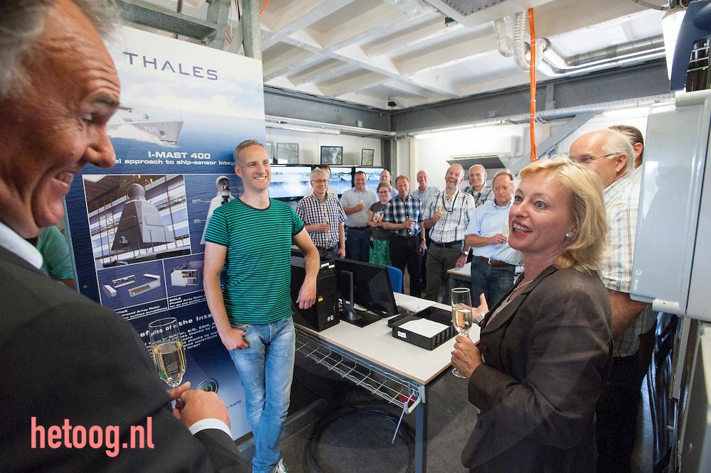 Nederland, Hengelo (O) 07juli2014  - Jet Bussemaker minister van onderwijs krijgt een rondleiding in de z.g.n. I-Mast van Thales bestemd voor de  schepen uit de 'holland klasse' van de koninklijke marine.  Hier toost zij samen met CEO Edelijn van Thales (links) Deze mast is bestemd voor de     ZR. MR. Friesland.                                  (volgende tekst is persbericht ministerie OCW):  Minister Jet Bussemaker (Onderwijs) stelde maandag 7 juli samen met een aantal vrouwelijke medewerkers de 5e I-mast in bedrijf bij Thales te Hengelo. Thales Nederland ontwikkelt geïntegreerde I-masten voor marineschepen van de zogenaamde Hollandklasse. In deze maststructuur zijn vrijwel alle sensoren en communicatiesystemen aan boord van het schip geïntegreerd. Het zijn de ogen en oren van het schip. Thales is als werkgever aangesloten bij het Techniekpact en zet zich in om meer vrouwen voor de techniek te interesseren. Het bedrijf is op dit moment bezig met een campagne om jonge vrouwen te interesseren voor techniek door jaarlijks 10 scholarships aan te bieden aan vrouwen die in de laatste twee jaar van hun studie zitten. Minister Bussemaker wil dat meer jongeren voor een technische opleiding kiezen. Het aantal studenten dat kiest voor een technische opleiding stijgt. fotografie Cees Elzenga/Hollandse -Hoogte