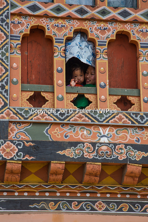 A small child her mother look out a window in Punakha, Bhutan.  The window is traditional Bhutanese architecture with Bhuddist religious symbols painted on the woodwork.