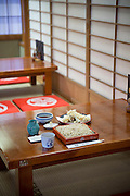 Traditional dining by the low tables on tatami floor and paper sliding doors at the Sarashina Horii Noodle Restaurant in Tokyo, Japan.