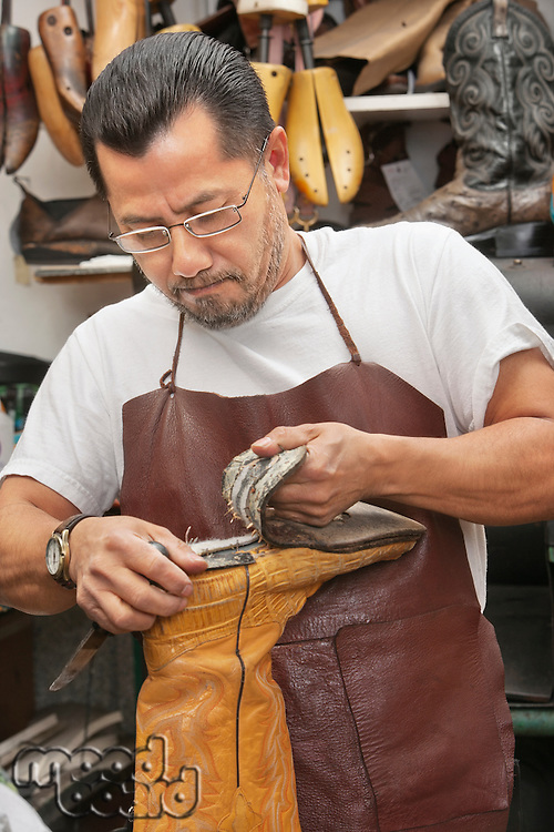 Mature shoemaker removing boot sole in shoe repair store