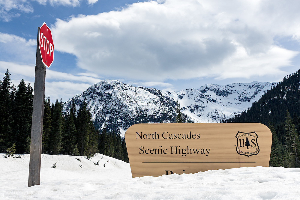 Signs at Rainy Pass in the North Cascades of Washington State, USA.  There is still deep snow along the side of the roads in early spring.