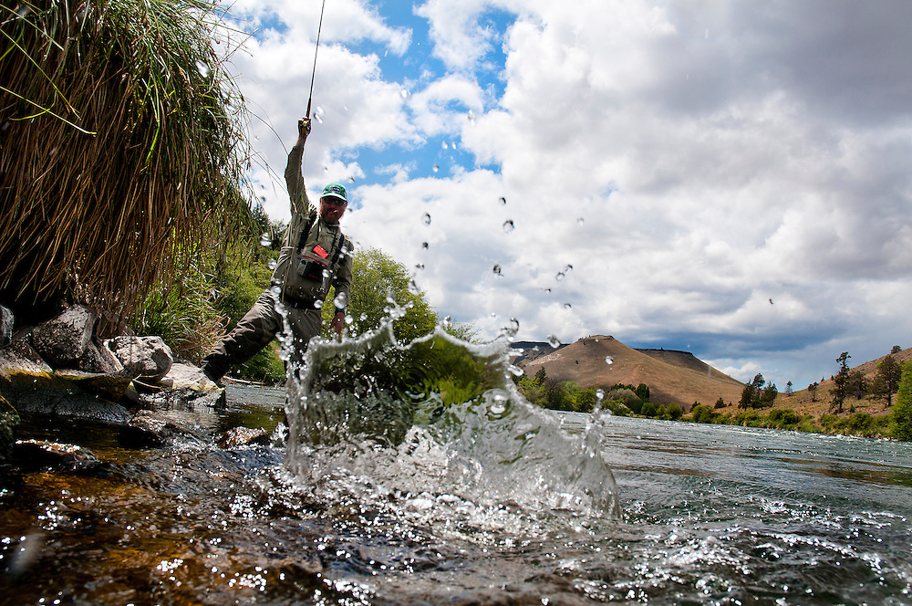Angler fighting fish in river