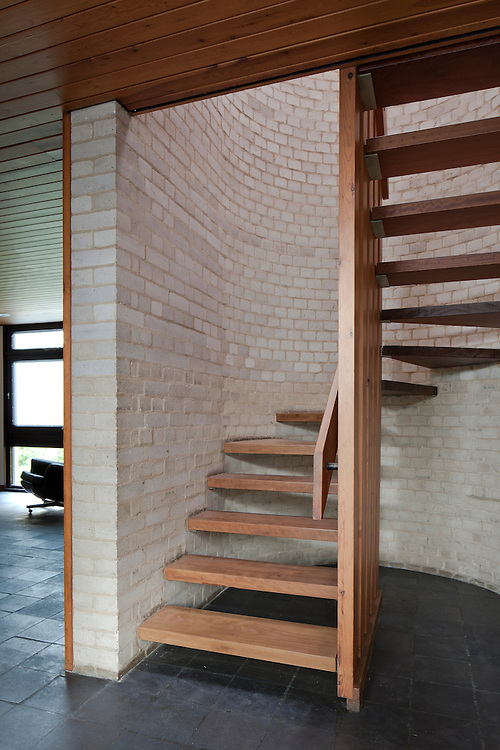 1960s wooden staircase with grey brick wall.