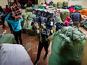 "22 DECEMBER 2017 - HANOI, VIETNAM: A woman carries a bundle of blue jeans in the wholesale clothes and fabric section of Dong Xuan Market in the old quarter of Hanoi. The old quarter is the heart of Hanoi, with narrow streets and lots of small shops but it's being ""gentrified"" because of tourism and some of the shops are being turned into hotels and cafes for tourists and wealthy Vietnamese.    PHOTO BY JACK KURTZ"