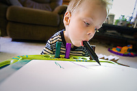 JEROME A. POLLOS/Press..Gavin Scheel, 2, uses his mouth to color with a marker Friday at his home in Careywood. Scheel  was born with Arthrogryposis, a rare congenital disorder that occurs in one in 3,000 births, and does not have the use of his arms or legs.