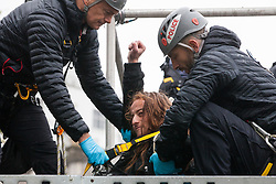 London, UK. 7 October, 2019. A climate activist from Extinction Rebellion makes a raised fist salute as a specialist team of Metropolitan Police officers works to remove him from a scaffold tower used to block Trafalgar Square on the first day of International Rebellion protests to demand a government declaration of a climate and ecological emergency, a commitment to halting biodiversity loss and net zero carbon emissions by 2025 and for the government to create and be led by the decisions of a Citizens' Assembly on climate and ecological justice.