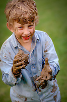 Smiling, young, mischievous boy playing with mud.