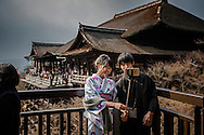 Young tourists, dressed in traditional Japanese clothing (the woman is wearing a kimono and the man, a hakama) using a selfie stick for a snapshot at Kiyomizu Temple, a world heritage site and huge tourist draw in Kyoto.  Rentals of tradional Japanese clothing are especially popular with Chinese tourists, slightly ironic given China's resentment of Japanese colonialism, the time such clothing would have defined the colonizer.  Kyoto, Japan  <br /> <br /> Recently selfie sticks were banned by West Japan Railway Co. (JR West).  &quot;The sticks annoy other commuters, JR West said.   Many tourism facilities because of the risk of electricution or even their use to make secret photos, like at onsen hot springs where genders, soaking without clothing, may only be protected from view by a low wall.