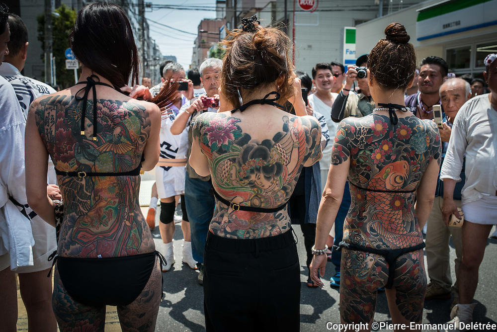 TOKYO, JAPAN - MAY 14: Yakuza members proudly display their tattoos during the second day of the Sanja Matsuri Festival in Tokyo's Asakusa district on May 14, 2016. This festival is one of the rare times when members of the notorious Yakuza gang reveal themselves to public and take photo with festival goers.