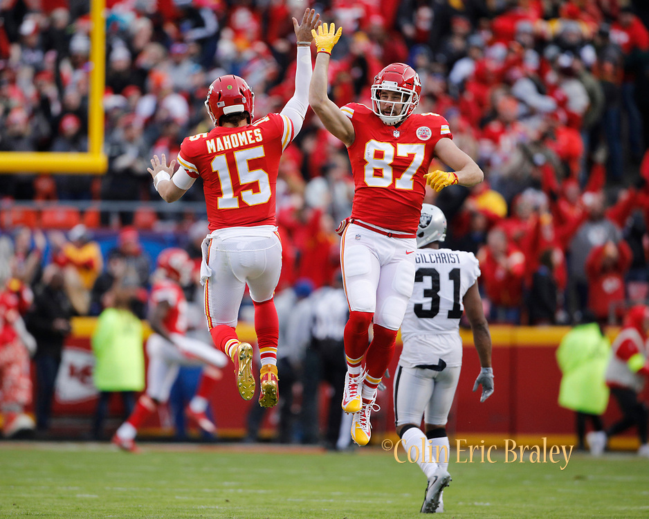 Kansas City Chiefs quarterback Patrick Mahomes (15) celebrates with tight end Travis Kelce (87) after throwing a 67-yard touchdown pass to Tyreek Hill during the first quarter of an NFL football game against the Oakland Raiders in Kansas City, Mo., Sunday, Dec. 30, 2018. Mahomes threw for 281 yards in the game, joining Peyton Manning as the only two QB's to reach over 5,000 passing yards and 50 touchdowns from the air in the same season. (AP Photo/Colin E. Braley)