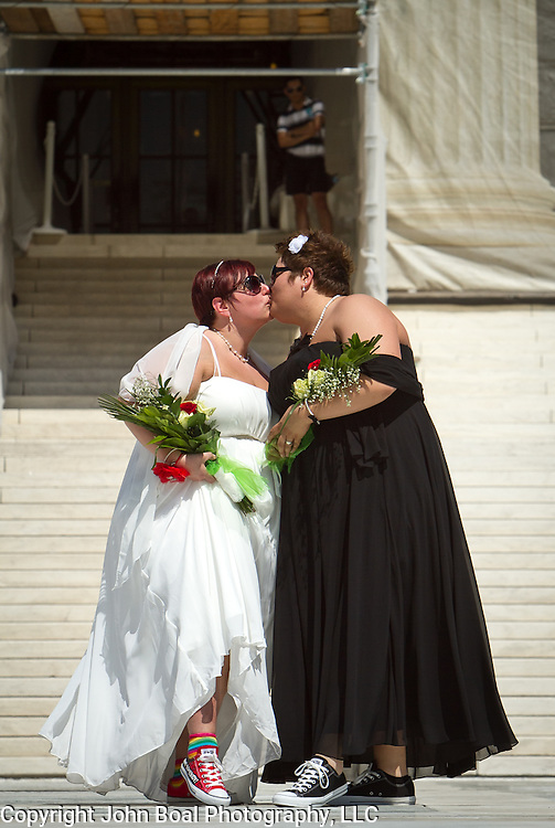 "Shannon Glatz, left, and Liberty Manos, of Akron Ohio, kiss to celebrate their marriage with twenty-four other couples as they traveled to Washington from Columbus Ohio, to get married en masse in front of the Supreme Court of the United States, on June 21, 2013.  Written along the bottom of Glatz's shoe is ""I Am Somebody"".  John Boal photography"