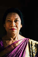 A portrait of a Nepalese woman in a purple sari.
