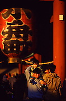 A father carries his young son through the gates of Senso-Ji shrine in Asakusa, Tokyo.