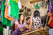 30 APRIL 2013 - MAHACHAI, SAMUT SAKHON, THAILAND: Burmese teen age girls chat on a tenement balcony above a fish processing plant in Mahachai, Samut Sakhon province, Thailand. The Thai fishing industry is heavily reliant on Burmese and Cambodian migrants. Burmese migrants crew many of the fishing boats that sail out of Samut Sakhon and staff many of the fish processing plants in Samut Sakhon, about 45 miles south of Bangkok. Migrants pay as much $700 (US) each to be smuggled from the Burmese border to Samut Sakhon for jobs that pay less than $5.00 (US) per day. There have also been reports that some Burmese workers are abused and held in slavery like conditions in the Thai fishing industry.         PHOTO BY JACK KURTZ