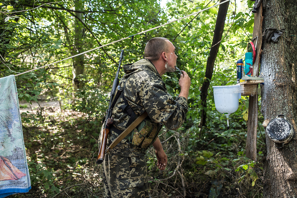 A pro-Russia rebel shaves at a camp by a checkpoint on the outskirts of the city on Monday, July 28, 2014 in Horlivka, Ukraine.