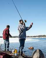 Matthew Cote casts his line from the shore of Lake Opechee at the Lakeport Dam with David Manita for opening day of landlocked fishing season.   (Karen Bobotas/for the Laconia Daily Sun)