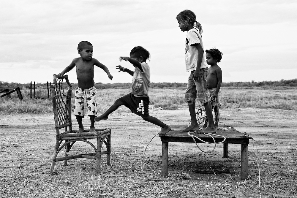 Children playing happily near Morgans Camp, which is the remain of an old Pearling Camp in the outskirts of Broome. Rainfall is rare in this part of the world . Broome, Western Australia. ©Ingetje Tadros/Diimex