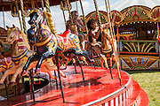 Women enjoying the Carousel in the steam fair. WOMAD 2014, festival of world music and dance, Charlton Park, Wiltshire. UK.