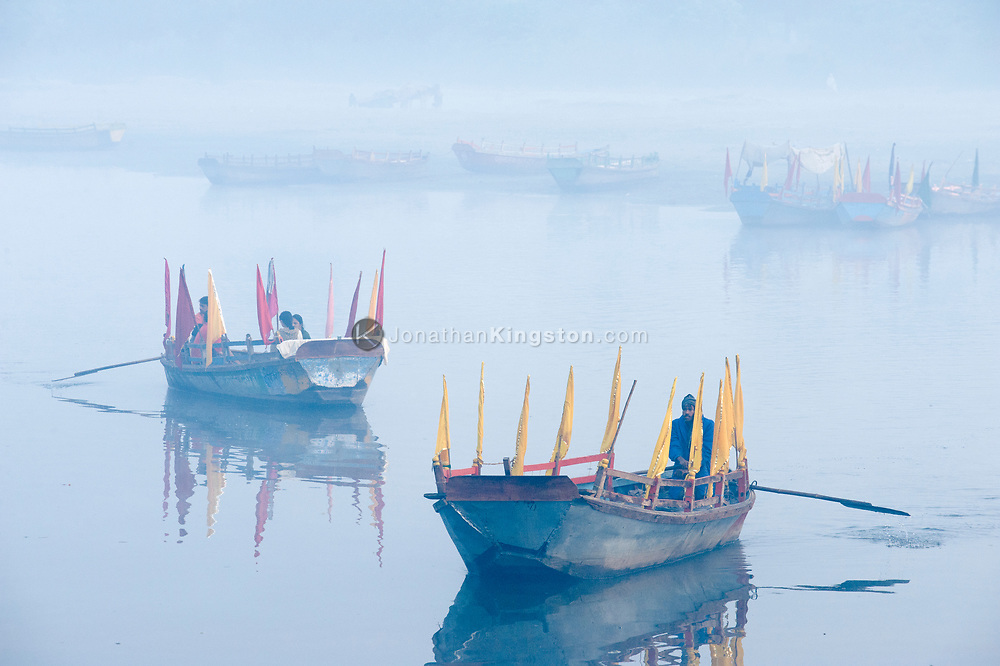 Boats on the Yamuna river at sunrise in Mathura, India.